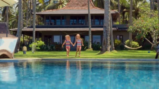 Zwei kleine Mädchen springen ins Schwimmbad