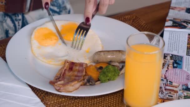 Žena ruce řezání smažené vejce na snídani