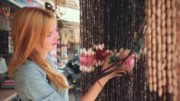 Young woman touching seashell curtain