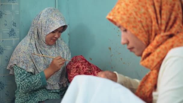 Két nő hajló, batik festés