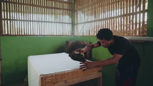 Indonesian man applying wax with cap to make batik