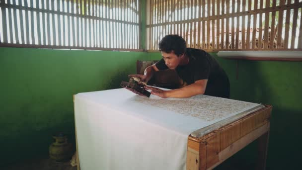 Indonesian man applying wax with cap to make batik