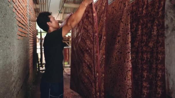 Indonéz ember vesz szárított batikolt szövetből kötél