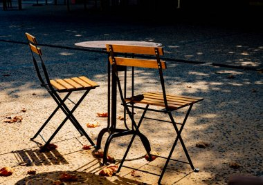 Two bistro chairs and a table in autumn