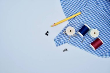 red, pink, blue and green thread with skirt hooks and eyes with yellow pencil on the blue checked fabric on the white background