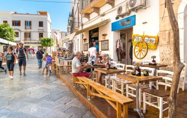 Favignana, Trapani, Italy - September 22, 2016: Tourists enjoying the coastline at the restaurant in the center of Favignana island, is the largest of the three Aegadian islands.