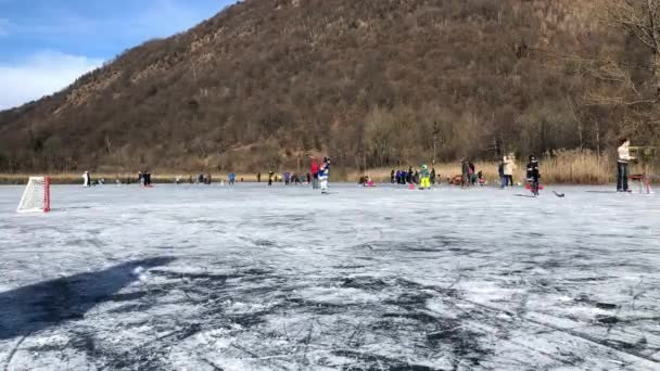 Ganna, Varese, Italy - January 19, 2020: People having fun on the frozen lake Ganna at winter day, in province of Varese, Italy, Time-Lapse