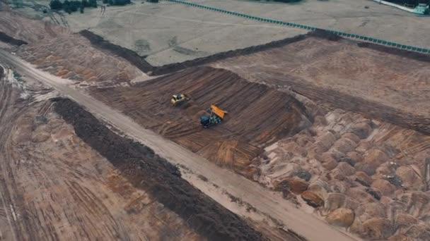 Bulldozer schaufelt Sand in einem Sandbruch auf der Baustelle