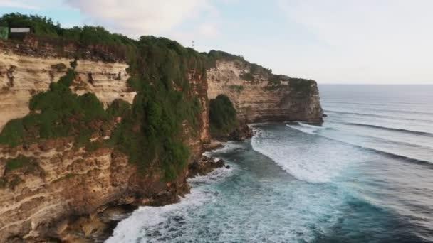 Top kilátás a drón a csodálatos szikla a tenger partján borított növényzet és növényzet.