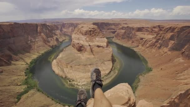 Tourist resting and looking at Horseshoe Bend and the Colorado River in the background, Arizona