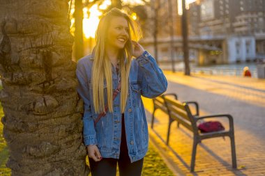 portrait of young blonde woman in park at sunset