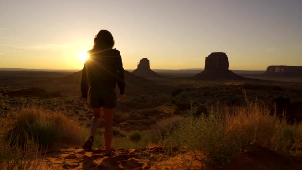 Mladá žena kráčející po rudém písku při východu slunce v Monument Valley v Utahu. Spojené státy