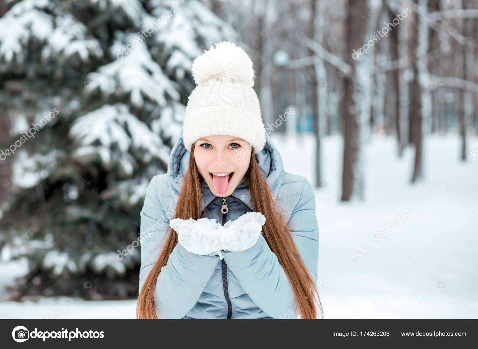 8eb6fa3dc A girl dressed in warm winter clothes and a hat posing in a winter ...