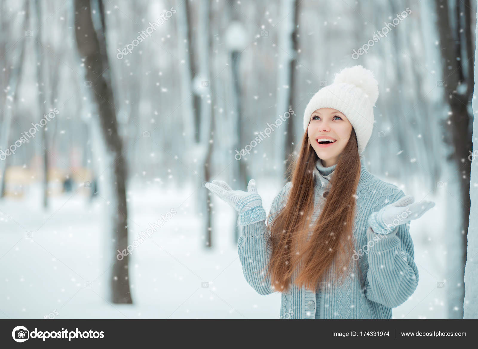 c862d63f2c1 Outdoor close-up portrait of young beautiful happy smiling girl holding snow  in hands. Dressed in winter clothes and a white hat