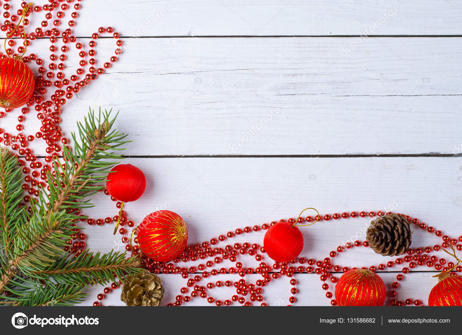 Christmas ornaments, beads and balls on a white wooden backgroun ...