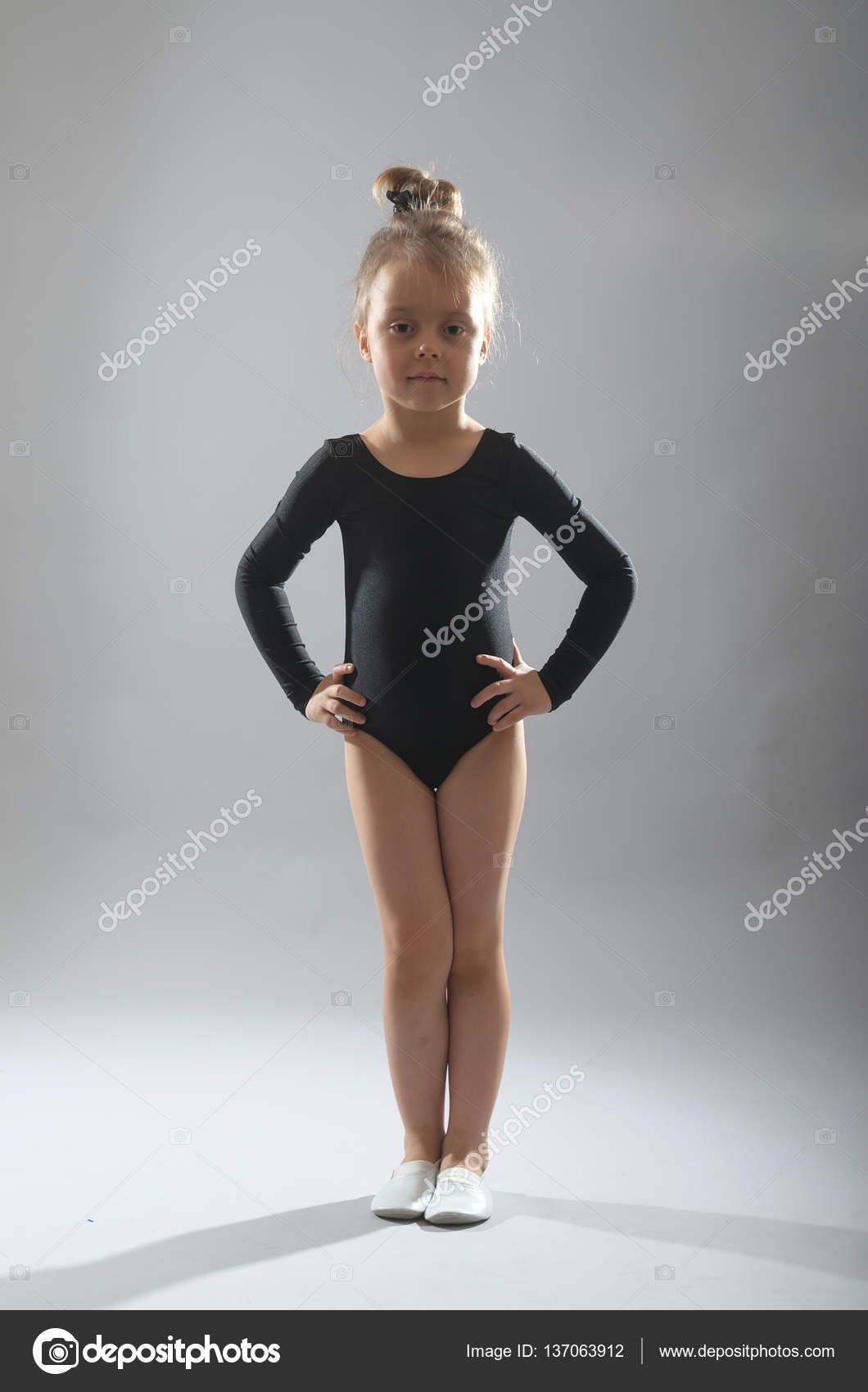 87d40ccca31a8 Kleines Mädchen in schwarzen Strumpfhosen tanzen auf einem grauen ...