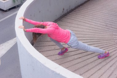 Young female runner prepairing for jogging in the city street. Fit body requires hard work. Urban sport concept. Young female exercising in sport clothes.