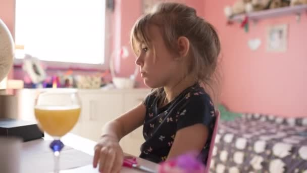 Beautiful little girl sitting on the desk in her room drawing and drinking orange juice