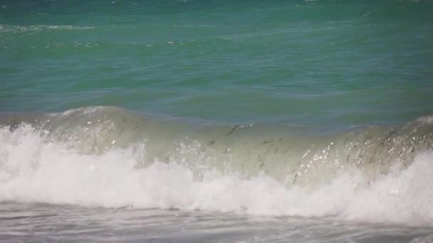 Zblízka vln narážejících na prázdnou pláž, zpomalený pohyb