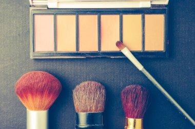 Makeup brushes and palette on black background, Vintage tone.