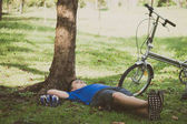A young man is relaxing after cycling in a park.