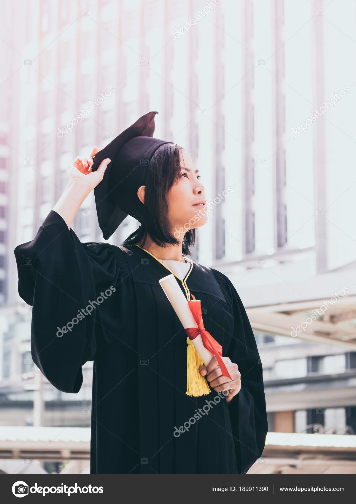 Graduation day, Asian woman with graduation cap and gown holding ...
