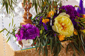 Floral arrangement to decorate wedding table in purple color. Th