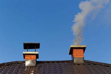 Smoke from brick chimney on roof against blue sky stock vector