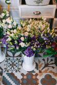 Krásné čerstvé květiny v květináčích v květinářství s krásné zdobené vintage podlahou