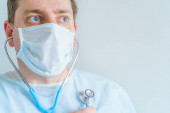 Orvos orvosi köntösben, arc maszk sztetoszkóppal. Hős fáradt a munkában, kétségbeesésében a kezelés a beteg betegek a kórházban. Küzdelem a koronavírus covid-19.Világ járvány veszélyes fertőzés.