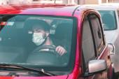 férfi védő maszk ül az autóban a dugóban, és előre néz