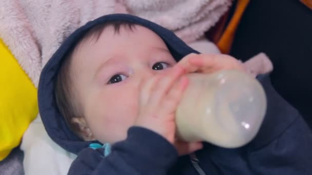 Baby boy drinks milk from a bottle close-up