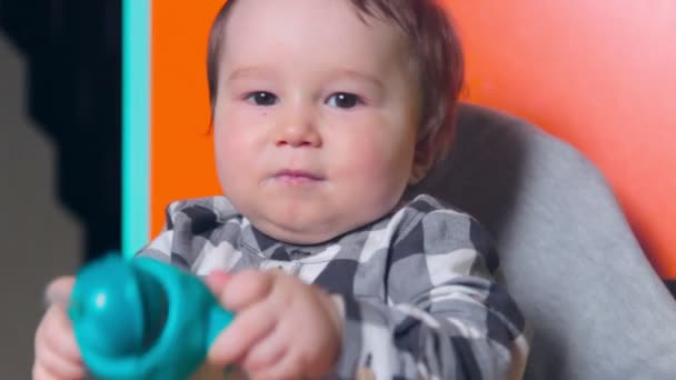 The child plays with a bottle for feeding in a chair for feeding.