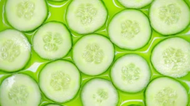 Közelkép. az uborka szeletek zöld alapon forognak. felülnézet