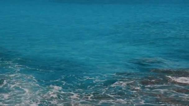 Modré vlny moře omývají břeh