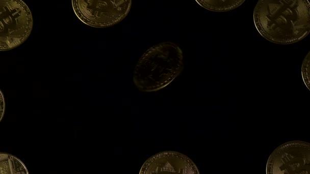 Draufsicht auf einen sich drehenden Bitcoin, der nach Stopps auf schwarzem Hintergrund leuchtet.