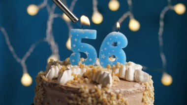 Birthday cake with 56 number candle on blue backgraund set on fire by lighter. Close-up