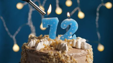 Birthday cake with 72 number candle on blue backgraund set on fire by lighter. Close-up