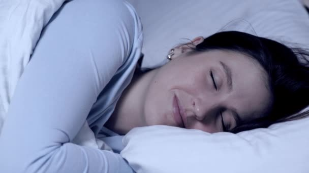 Girl sleeping and smiling. Sweet dreams concept. Young attractive caucasian girl sleeps alone in bed hugging pillow and experiences positive emotions. Close-up