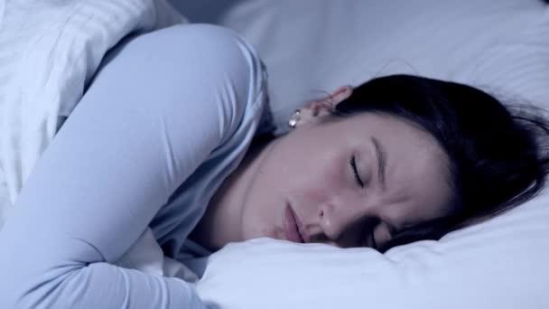 Dívka spí a mračí se. Koncept nočních můr a zlých snů. Mladá atraktivní běloška spí sama v posteli a zažívá negativní emoce ze snů. Detailní záběr