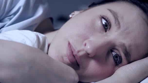 Dívka v noci pláče. Odpor, frustrace, problémy v osobním životě, problémy v pojetí vztahů. Atraktivní mladá žena leží v posteli a po tváři jí stékají slzy. Detailní záběr
