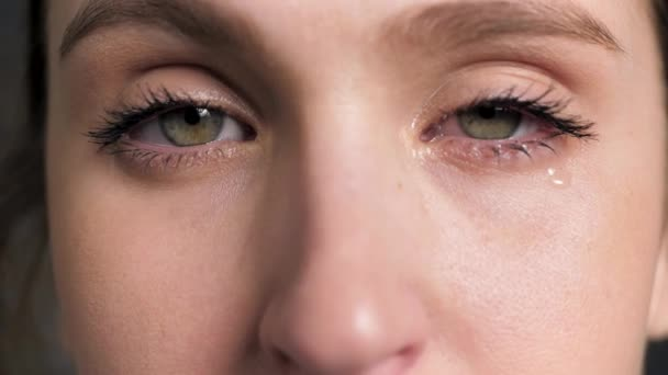 Watery eyes. Woman cries and looking at camera, flu, tonsillitis, colds, conjunctivitis, blepharitis, allergy, sinusitis, dacryocystitis, inversion of eyelids concepts. Front view. Close-up