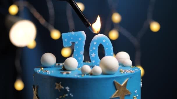 Geburtstagstorte Nummer 70 Sternenhimmel und Mondkonzept, blaue Kerze wird mit Feuerzeug angezündet und dann ausgeblasen. Kopieren Sie ggf. den Speicherplatz auf der rechten Bildschirmseite. Nahaufnahme und Zeitlupe
