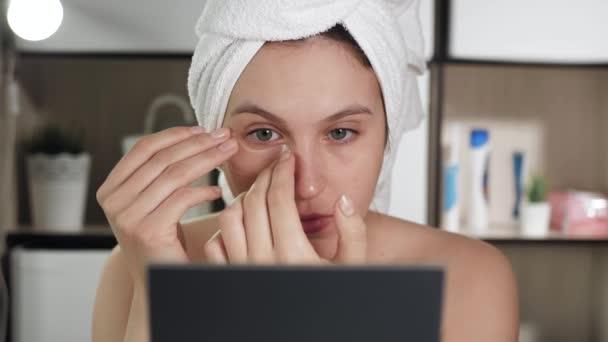 Pásky na oči. Atraktivní žena v koupelně s ručníkem na hlavě si přilepí průhledné skvrny na kůži pod očima. Hygiena, kosmetička, make-up, péče o obličej. Detailní záběr
