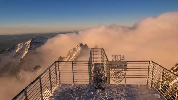 Timelapse 4k výhled Vysoko v horách. Nízko obrácené mraky projíždějící zasněženými horami.