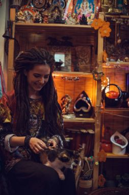 girl with dreadlocks holding cat