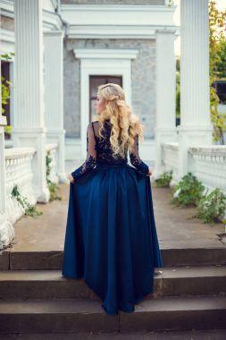 Full length portrait of blonde model girl posing in summer blossom park, back view stock vector