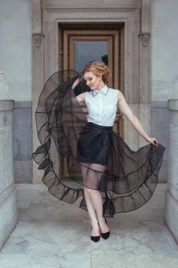 Blonde girl posing in white blouse and black skirt in Livadia palace, full length stock vector