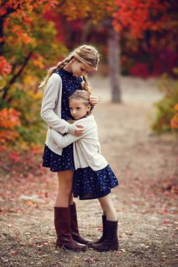 sisters hugging in park