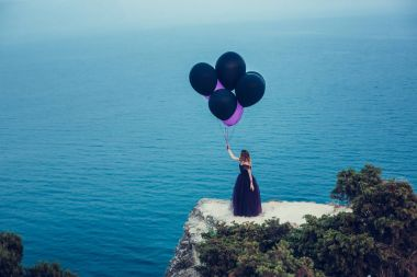 woman in dark dress holding balloons
